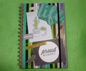 A photo, taken on a green blanket background, of a cardboard spiral-bound journal decorated with stripes of plain and glittery washi tapes in aro pride flag colours. The cover displays with some journal card and scrapbook design pieces by Kaisercraft depicting arrows, cacti and typography over the tape stripes. There's aro pride colours in a matte paper tape, silver and two greens in holographic tape, and two narrow tapes in glittery silver and matte light green. The striped cover alternates between the matte tapes and the glittery tapes.