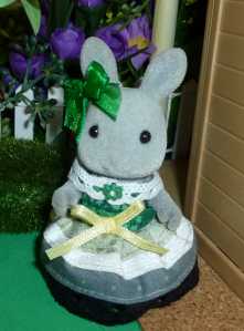 A close up photo of a grey Sylvanian Families rabbit doll/figurine standing beside a plastic faux-wood wall against a background of fake foliage, purple fabric flowers, a white picket fence and a fuzzy green bush. The rabbit is wearing a handsewn dress in the colours of the aro pride flag: a dark green waistband with light green, white and grey stripes followed by a black lace trim. A yellow ribbon is sewn to the front of the dress and she wears a green ribbon bow on one of her ears.