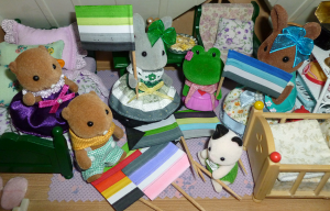 A group of Sylvanian Families animal figurines in a dollhouse bedroom, either holding aro-spec pride flags or sitting around a pile of pride flags on the floor. Flags include aro, fray, akoi/lith, cupio, demi and quoi, and animal figurines include two brown beavers, a grey rabbit, a green frog, a brown rabbit and a black-and-white cat baby. The grey rabbit, holding an aro pride flag, is wearing a striped dress in aro-pride colours.
