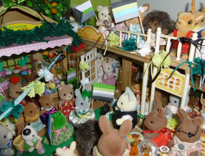 A photo showing a Sylvanian Families village, comprised of a bakery and a florist. The village is crowded with small animal figurines set up to be either marching in a parade or waving the parade on from the sidelines, with many figures carrying handdrawn aro, akoi/lith, greyro, demiro, fray, cupio and quoi pride flags. Coloured pompoms in dark green, light green and white decorate railings and doorways, coloured bows in aro-pride colours decorate roofs and railings, and a banner comprised of pompoms and bows stretches from the corner of the house to the corner of the bakery, across the small village square. Animal figures include hedgehogs, rabbits, deer, cats, mice, dogs, beavers, bears and a frog.