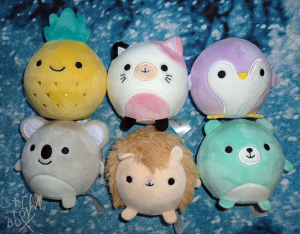 a photo of two rows of six spherical squishy plush sitting on a mottled blue and white quilt cover. The plush have small round eyes in black thread with other embroidered facial features like noses, whiskers and beaks, with tiny, undersized ovals of plush sticking out for arms, wings and legs. From left to right, top to bottom: a yellow and green pineapple; a black, pink and white calico cat; a purple and white penguin; a grey koala; a brown and cream hedgehog; and a white and aqua bear.