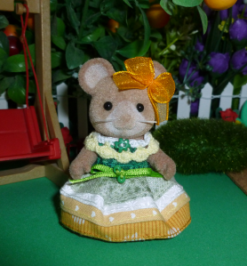 A photo focused on a brown mouse Sylvanian Families mouse doll/figurine standing beside a plastic faux-wood wall against a background of fake foliage, purple fabric flowers, a white picket fence, a red swing set and a fuzzy green bush. The mouse is wearing a handsewn dress in the colours of the allo-aro pride flag: a dark green waistband with a skirt of light green, white, yellow and gold quilting cotton stripes. A green ribbon is sewn to the front of the dress, with two small green beads, and she wears a gold ribbon bow on one of her ears.