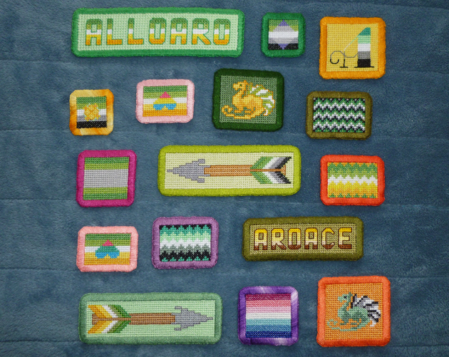 "An assortment of cross stitch patches with wide hand-embroidered borders in rectangluar and square shapes. Patches include various aromantic-spectrum flags in straight and zigzag lines, text patches ""alloaro"" and ""aroace"", arrow patches, patches with pan/ply hearts atop the allo-aro flag, dragon patches in flag colours and a calligraphic style letter A in aro colours."